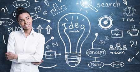 A female entrepreneur ponders a diagram on a chalkboard